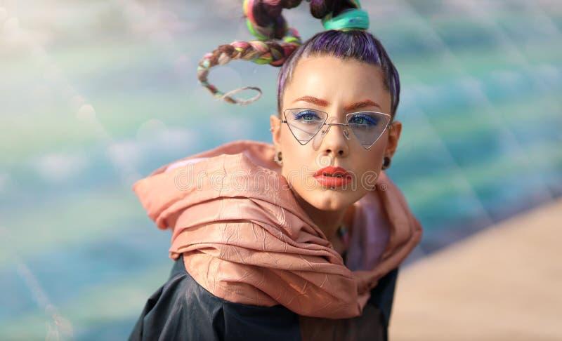 Het meisje van het avantgardeportret met ongebruikelijk maakt en stelt zich omhoog zonglas voor Portret van het jonge vrouw koele royalty-vrije stock foto