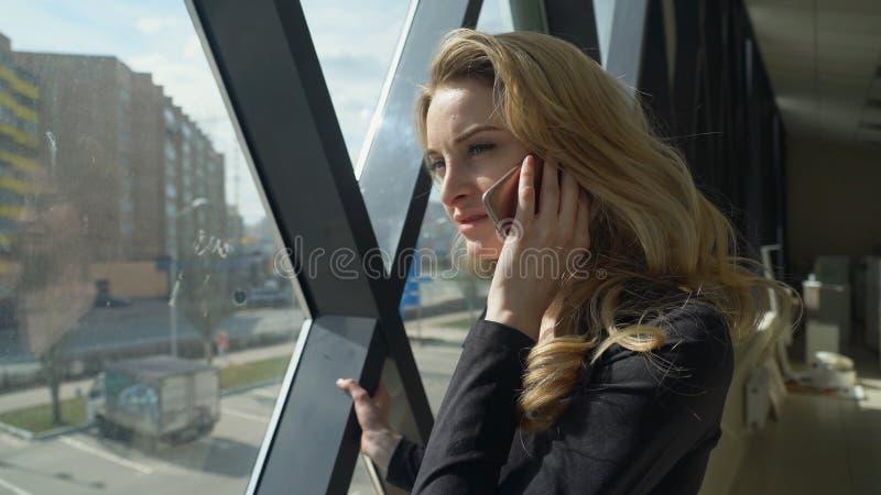 Het meisje van het Beautisulblonde in het zwarte lopen door het venster en het spreken op de telefoon royalty-vrije stock foto