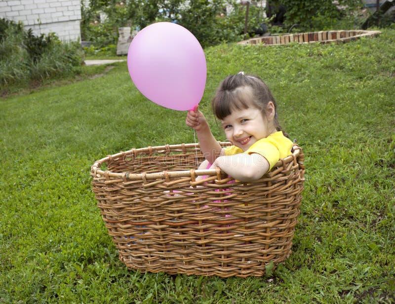 Het meisje van de baby in de mand met de bal stock fotografie