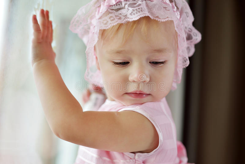 Het meisje van de baby dichtbij het venster stock afbeeldingen
