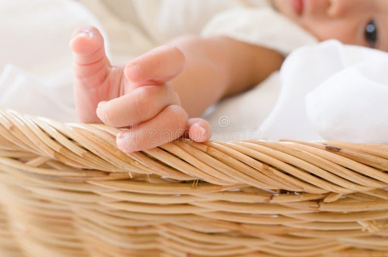 Het meisje van de baby in een mand Selectieve nadruk op hand stock fotografie