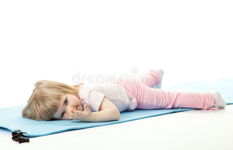 Het meisje van de baby het ontspannen na sport op een opleidingsmat royalty-vrije stock afbeelding