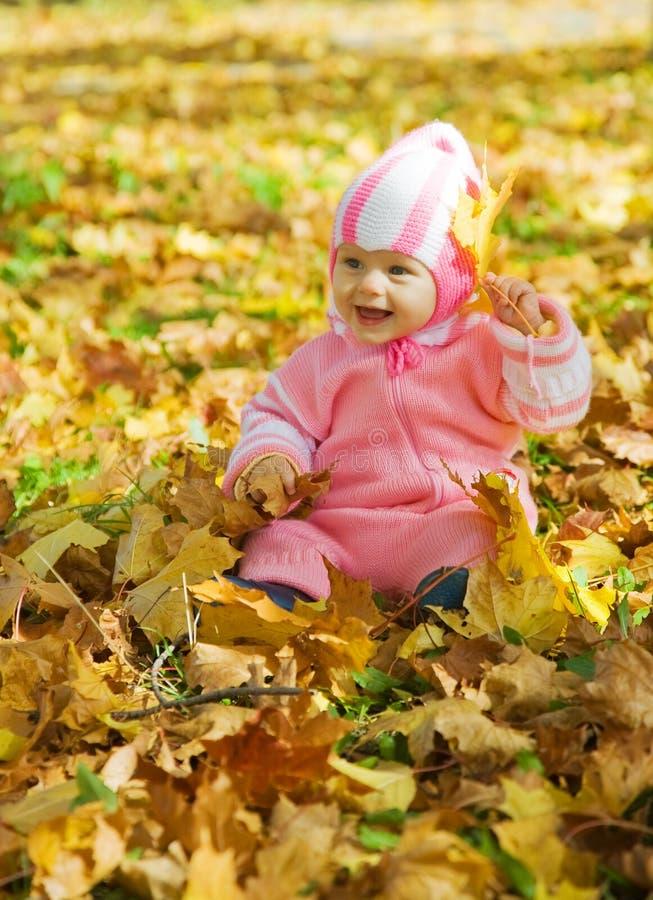 Het meisje van de baby het spelen met herfstbladeren stock foto's
