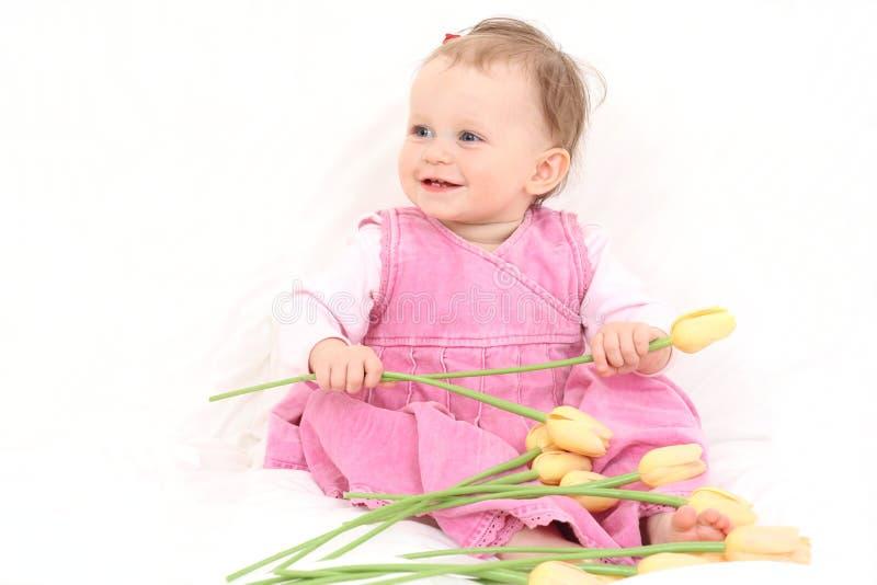 Het meisje van de baby met bloemen stock foto