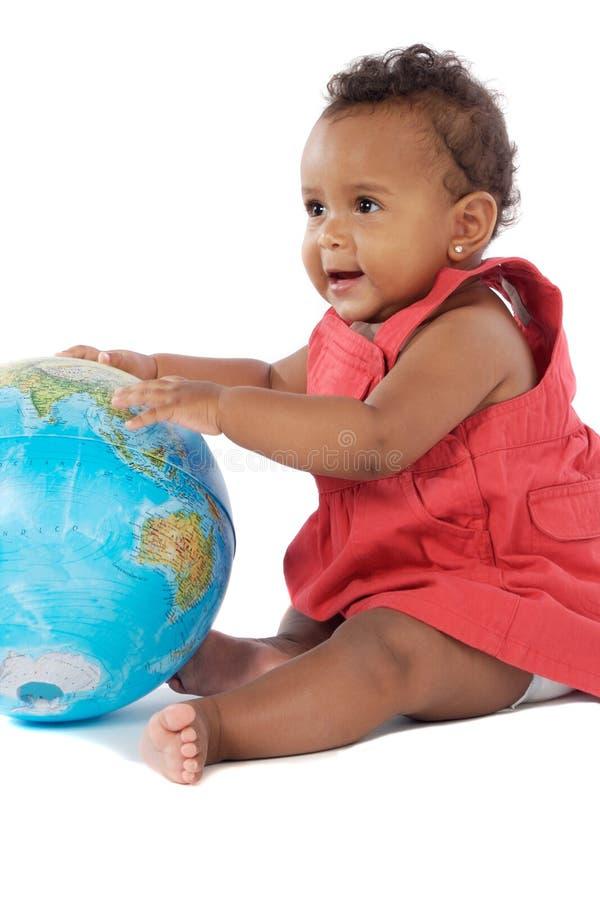 Het meisje van de baby met een bol van de wereld stock foto