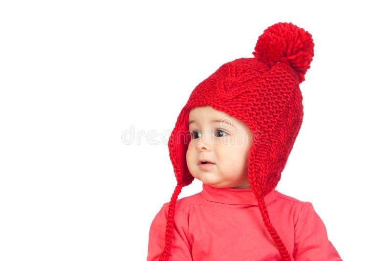 Het meisje van de baby met een grappige wol rode hoed stock foto's