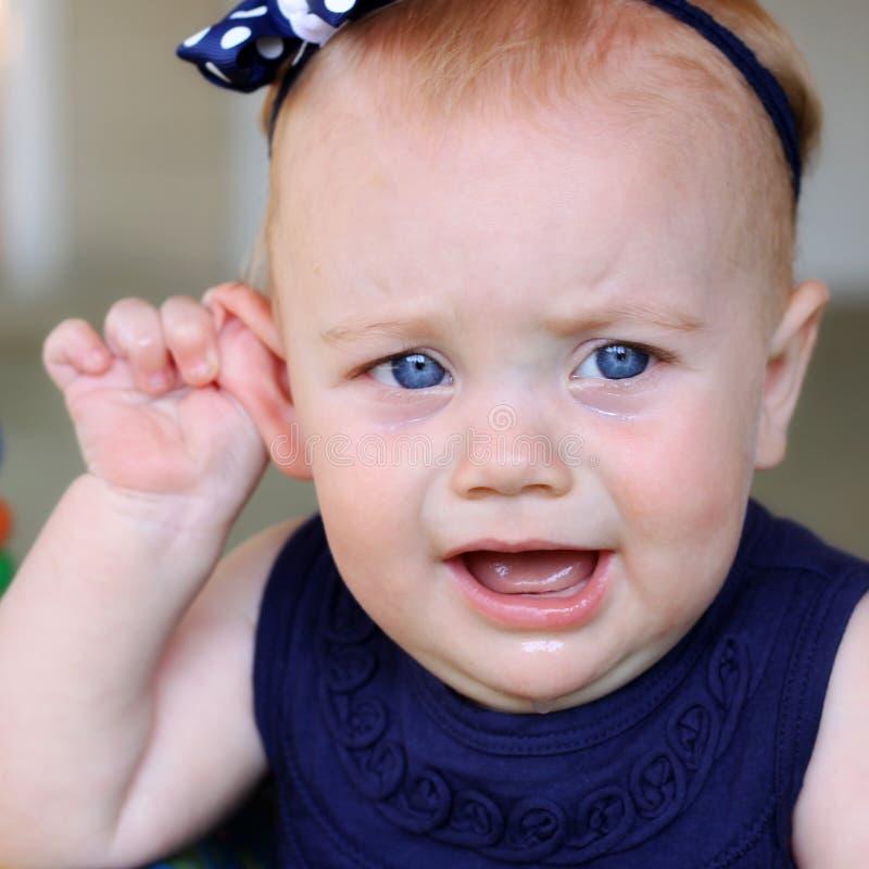 Het meisje van de baby met oorpijn stock afbeelding