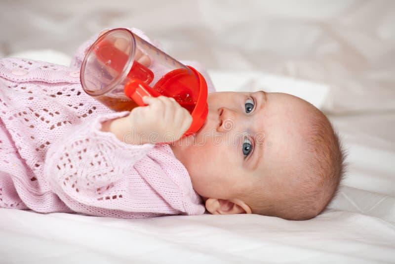 Het meisje van de baby met sippy kop stock afbeelding