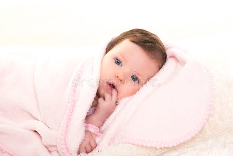 Het meisje van de baby met tandpijn in roze met wit bont stock foto