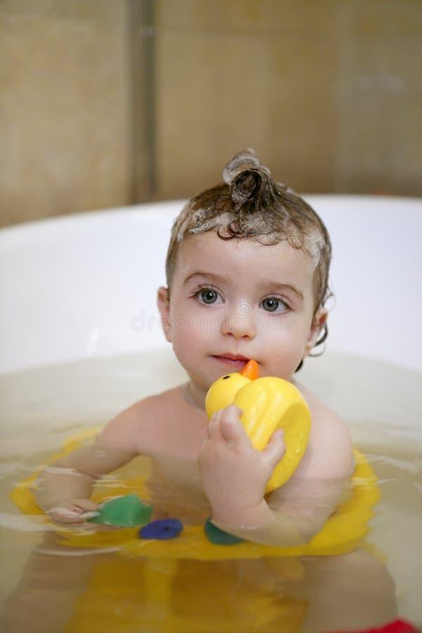 Het meisje van de baby op bad dat gele eend speelt stock fotografie