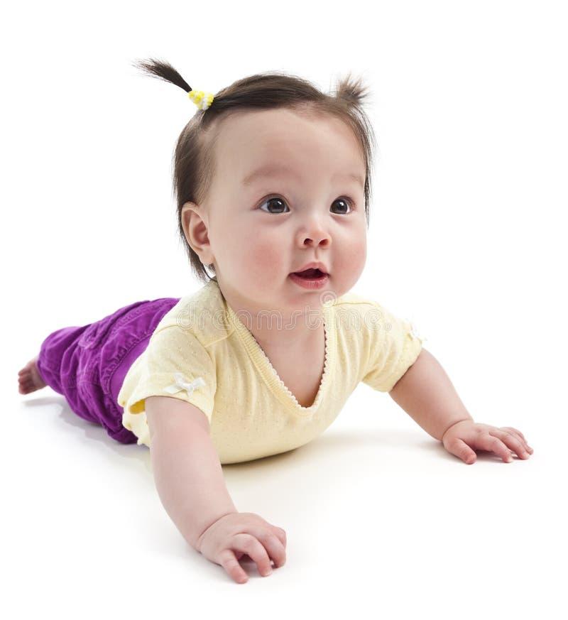 Het meisje van de baby op haar maag stock foto