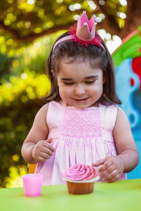 Het meisje van de babypeuter in openluchtpartij bij tuin, gelukkig en glimlachend bij cupcake met zoete tanduitdrukking royalty-vrije stock afbeeldingen