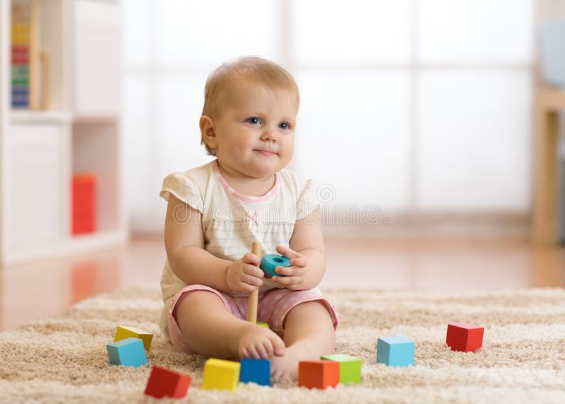 Het meisje van de babypeuter het spelen met houten speelgoed en het hebben van pret stock afbeelding