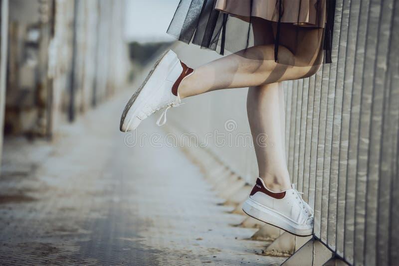 Het meisje van de benentiener in witte tennisschoenen op de brug stock foto's