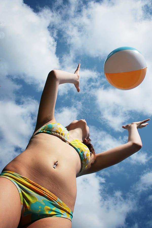 Het meisje van de bikini het werpen strandbal stock foto's