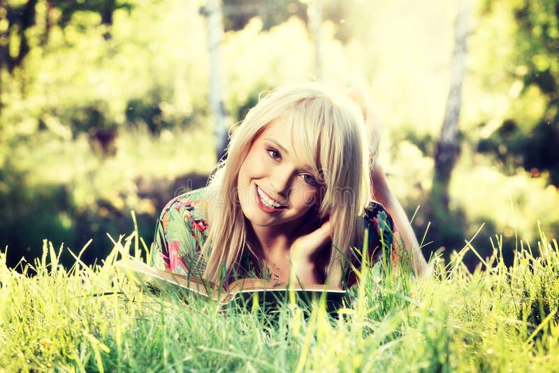 Het meisje van de blonde het jonge vrouw ontspannen in een boek van de parklezing, zitting alleen op gras royalty-vrije stock foto's