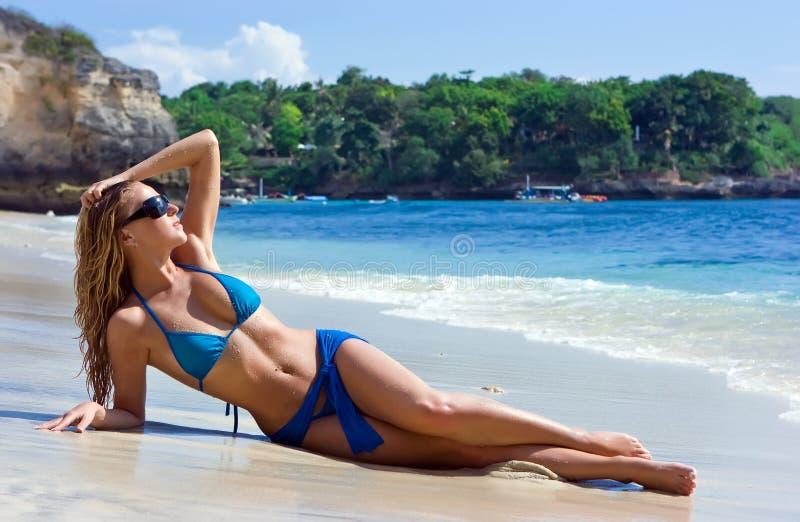 Het meisje van de blonde het ontspannen in water op het strand royalty-vrije stock afbeeldingen