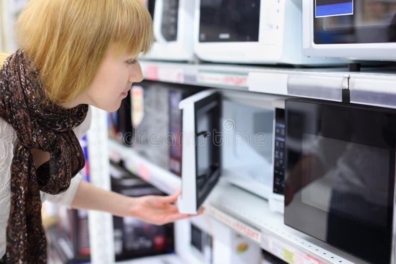 Het meisje van de blonde opent microgolf in winkel royalty-vrije stock fotografie