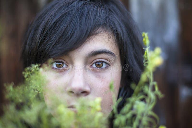 Het meisje van de close-uptiener met expressieve die ogen, in het groen van de tuin worden verborgen Emo royalty-vrije stock foto