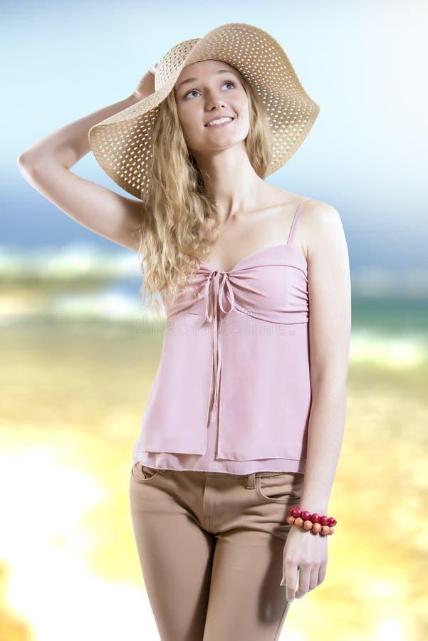 Het meisje van de de zomerescapist met strohoed op het strand royalty-vrije stock fotografie