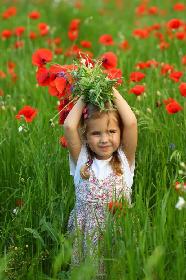 Het meisje van de drie éénjarigenpeuter op het de zomergebied van bloeiende papavers stock afbeeldingen