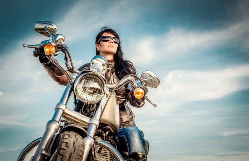 Het meisje van de fietser op een motorfiets stock foto