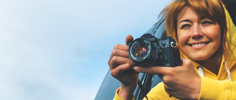 Het meisje van de glimlachtoerist in een open venster van een autoauto die fotografie nemen klikt op retro uitstekende fotocamera stock afbeeldingen