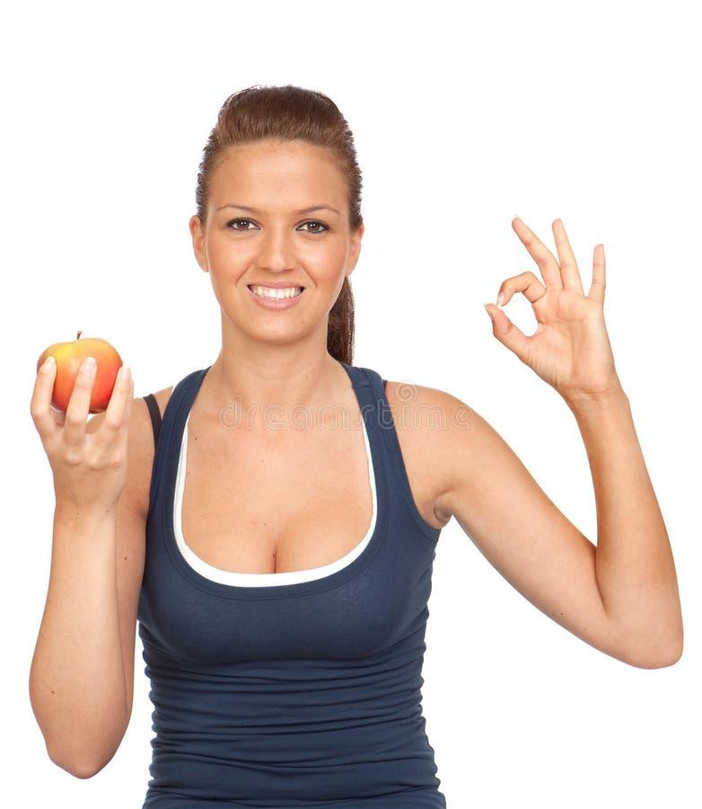 Het meisje van de gymnastiek met een appelzitting die o.k. zegt royalty-vrije stock afbeeldingen