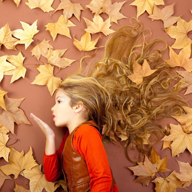 Het meisje van de herfst op droge bladeren die windlippen blazen royalty-vrije stock fotografie