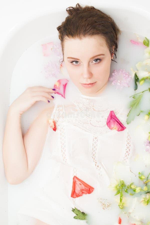 Het meisje van de kuuroordschoonheid het baden in melkbad, kuuroord en het concept van de huidzorg Schoonheids jonge Vrouw met pe stock afbeelding