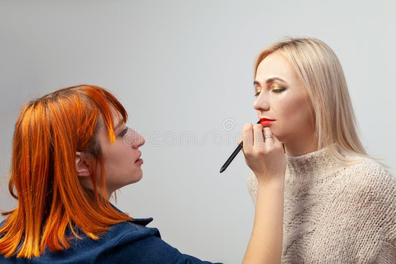 Het meisje van de make-upkunstenaar met rood haar zet rode lippenstift op de lippen van een blonde modelzitting met gesloten ogen royalty-vrije stock foto