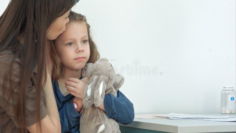 Het meisje van de moederholding en het vergen van haar temperatuur met thermometer op artsenkantoor royalty-vrije stock foto