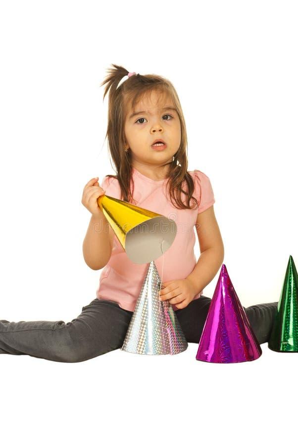 Het meisje van de peuter het spelen met partijhoeden stock afbeelding