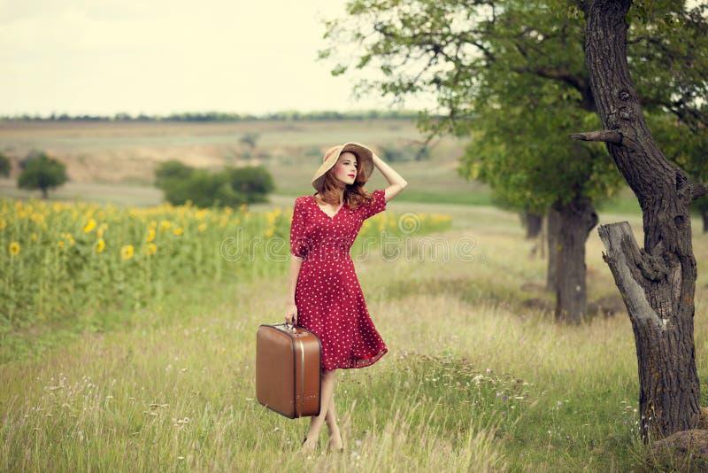 Het meisje van de roodharige met koffer bij openlucht. stock foto