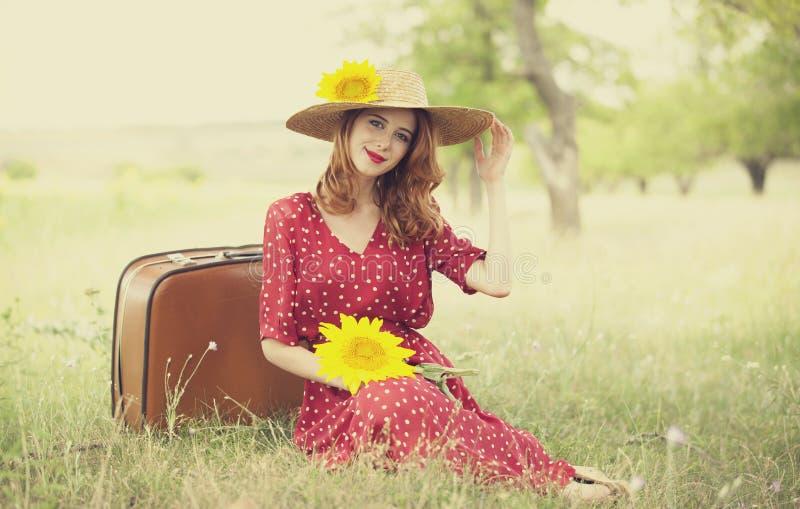 Het meisje van de roodharige met zonnebloem bij openlucht. stock afbeelding