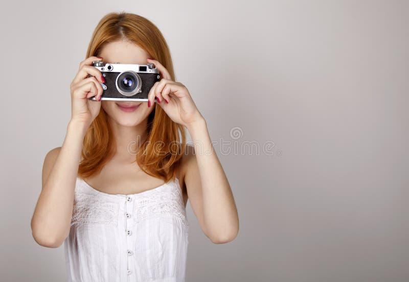 Het meisje van de roodharige in witte kleding met uitstekende camera. royalty-vrije stock afbeeldingen