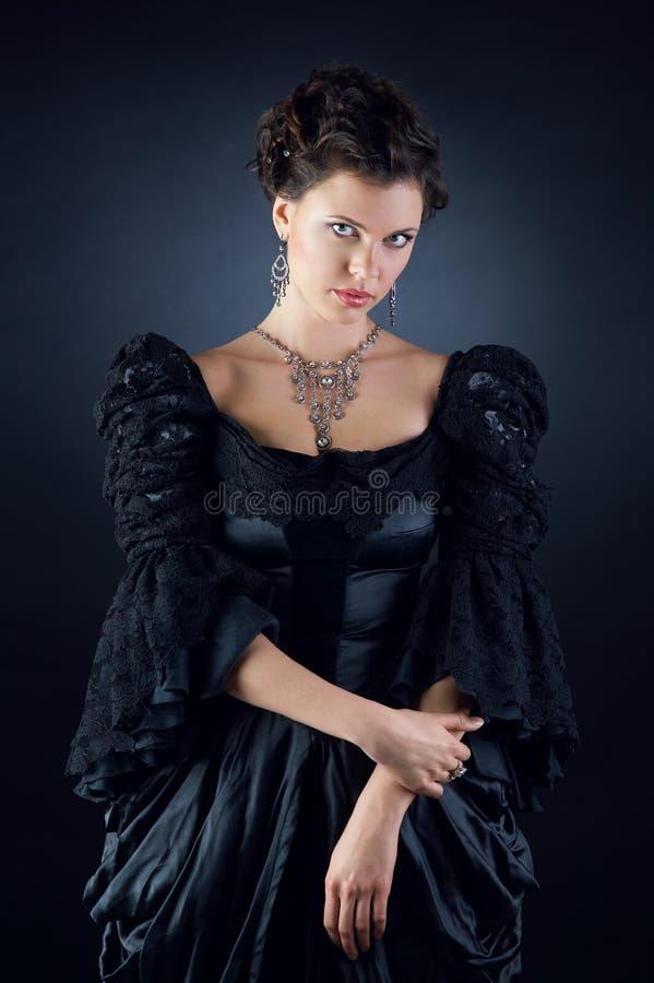 Het meisje van de schoonheid in een uitstekende zwarte kleding royalty-vrije stock afbeeldingen