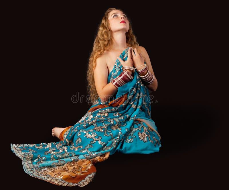 Het meisje van de schoonheid zit in Indisch kostuum met hartstocht stock foto
