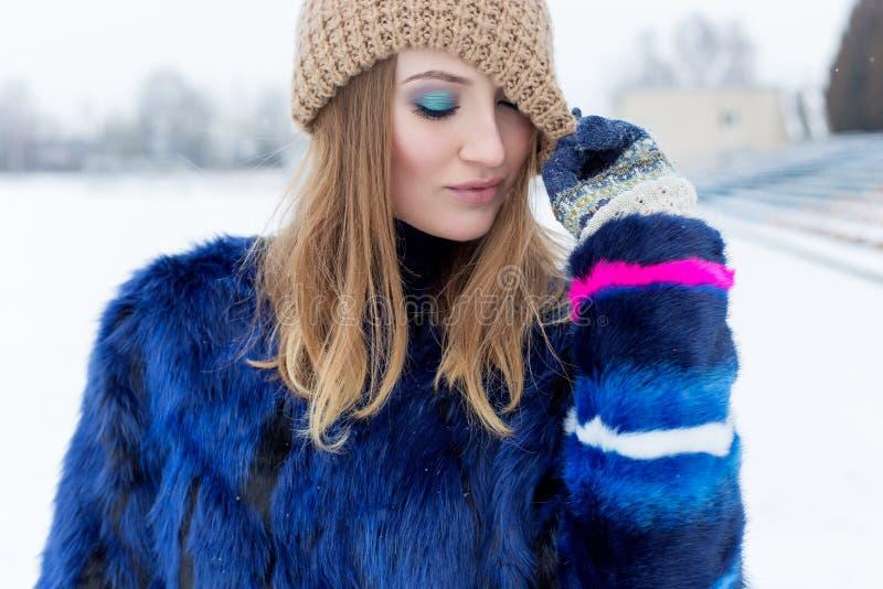 Het meisje van de schoonheidsmannequin in een bontjas Mooie donkerbruine vrouw met heldere make-up in heldere de winterdag stock foto's