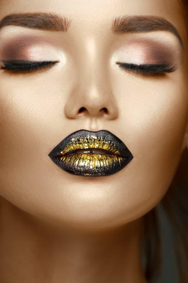 Het meisje van de schoonheidsmannequin met zwarte en gouden gradiëntlippen, In make-up, perfecte huid stock afbeeldingen