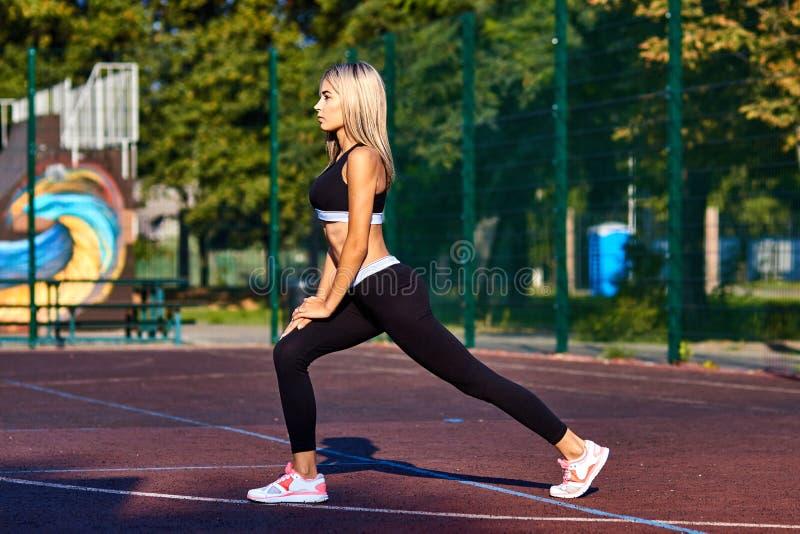 Het meisje van de sport Het meisje doet geschiktheidsoefeningen Mooie jonge sportenvrouw die oefeningen doen Een vrouw leidt op s stock foto