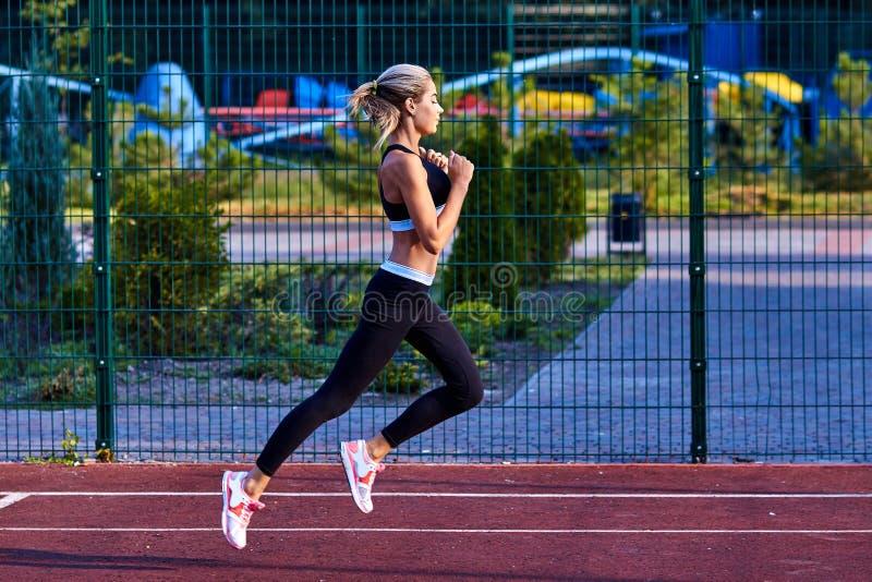 Het meisje van de sport Het meisje doet geschiktheidsoefeningen Mooie jonge sportenvrouw die oefeningen doen Een vrouw leidt op s stock foto's