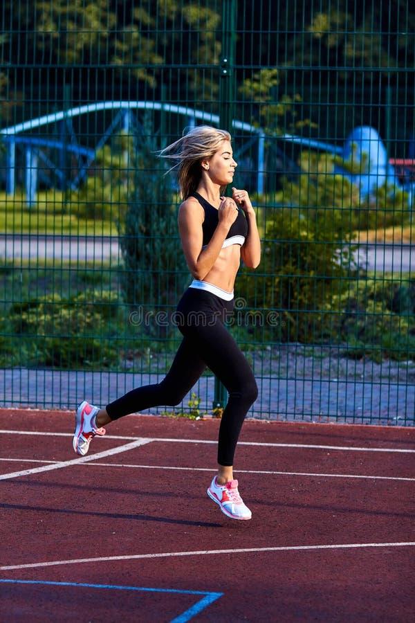 Het meisje van de sport Het meisje doet geschiktheidsoefeningen Mooie jonge sportenvrouw die oefeningen doen Een vrouw leidt op s stock afbeelding
