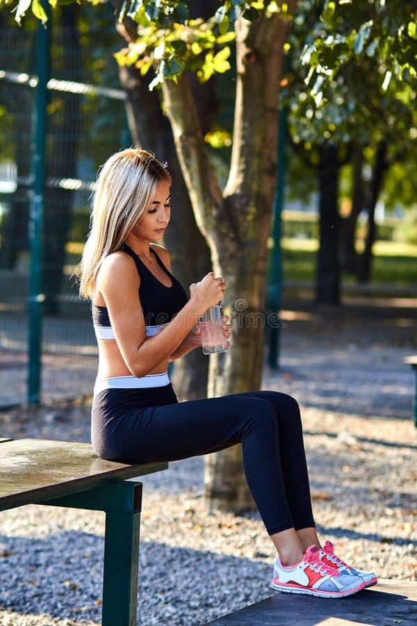 Het meisje van de sport Het meisje doet geschiktheidsoefeningen Mooie jonge sportenvrouw die oefeningen doen Een vrouw leidt op s stock fotografie
