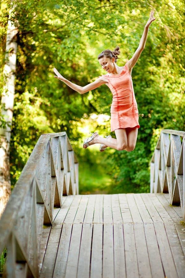Het meisje van de sprong op de zomerbrug stock foto