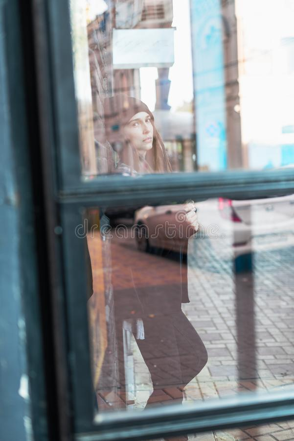 Het meisje van de straatstijl met dreadlocks achter glasdeur royalty-vrije stock afbeelding