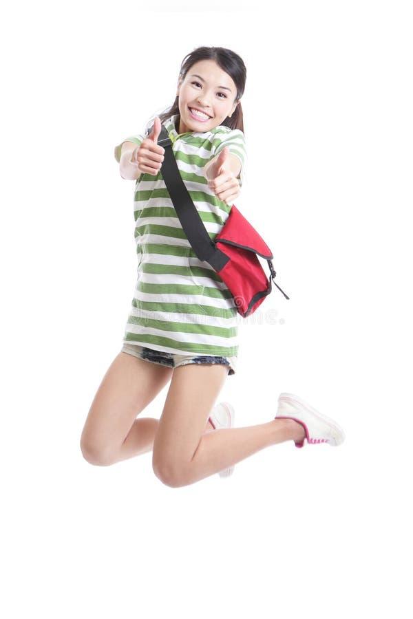 Het meisje van de student het springen en goed handgebaar royalty-vrije stock foto's