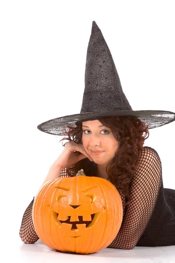 Het meisje van de tiener in de hoed van Halloween met gesneden pompoen royalty-vrije stock foto's
