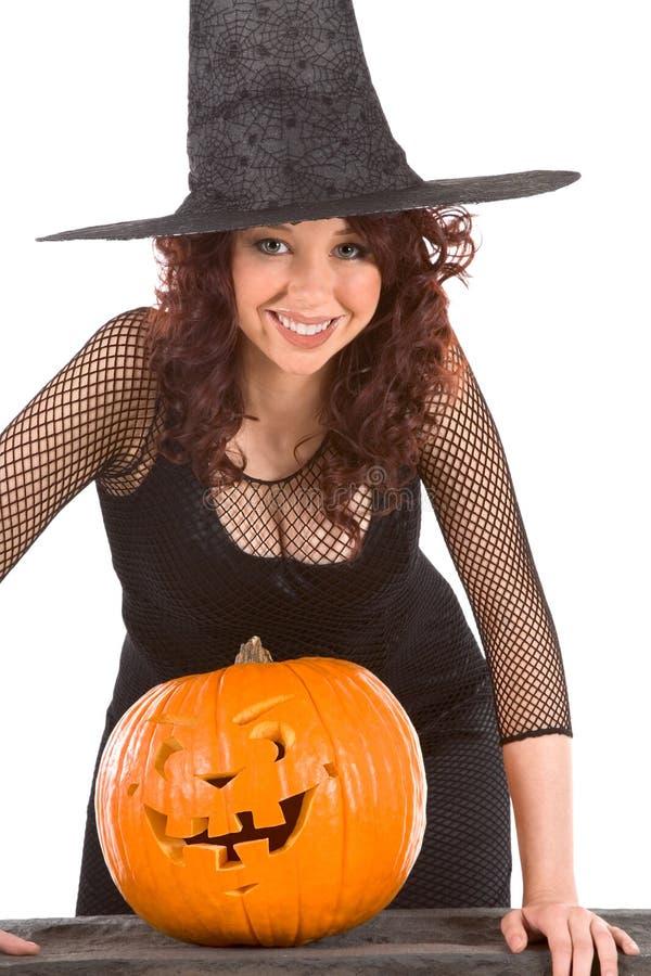 Het meisje van de tiener in de hoed van Halloween met gesneden pompoen stock fotografie