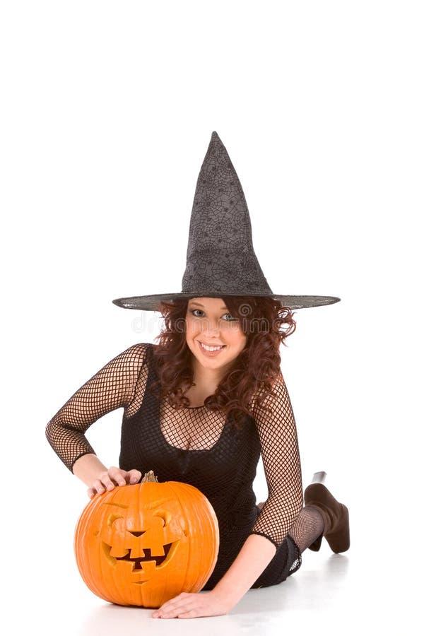 Het meisje van de tiener in de hoed van Halloween met gesneden pompoen royalty-vrije stock fotografie